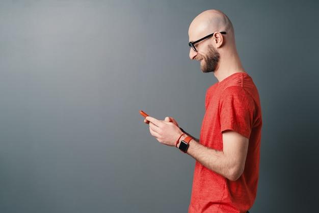 Вид сбоку улыбающийся красивый лысый мужчина с бородой, очками, красной футболкой и текстовыми сообщениями