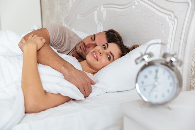 Side view of smiling lovely couple sleeping together in bed