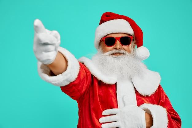 Vista laterale dell'uomo sorridente in costume rosso di babbo natale. ritratto isolato del maschio senior con la barba bianca lunga in occhiali da sole che indica via