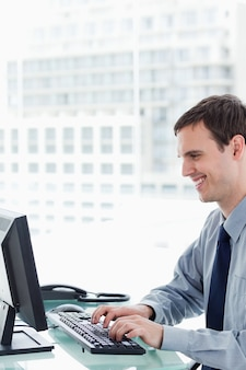 Side view of a smiling office worker using a monitor