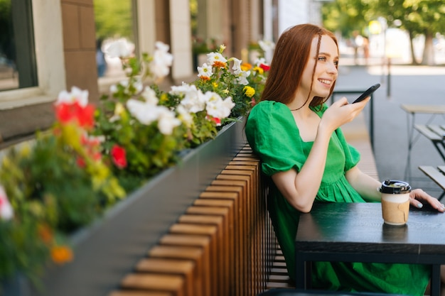 Side view of smiling redhead young woman recording audio voice message on cellphone sitting at table with coffee cup in outdoor cafe terrace in sunny summer day.
