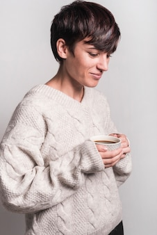 Side view of smiling sick woman holding coffee cup against white background