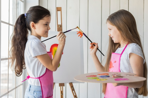 Side view of smiling two girls touching their paint brushes while painting on canvas