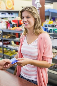 Side view of a smiling woman at cash register paying with credit card