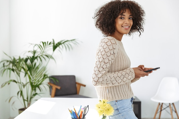 Side view of smiling woman wearing in casual clothes holding smartphone and looking at the camera while standing near the table at office