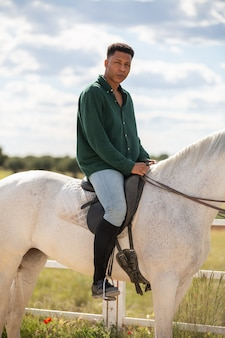 Side view of smiling young african american male looking at camera while sitting on back of white horse
