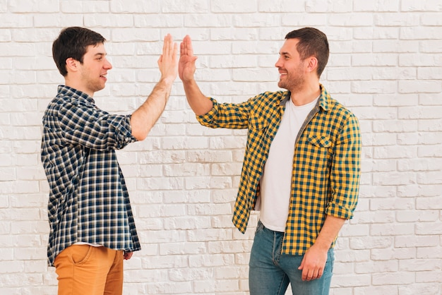 Side view of a smiling young male friends giving high five to each other
