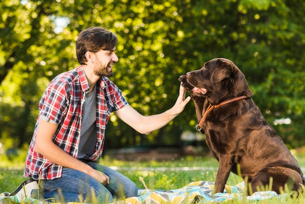 Side view of a smiling young man having fun with his dog in garden