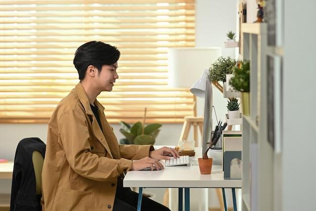 Вид сбоку улыбается молодой человек, работающий с компьютером в домашнем офисе.