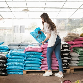Side view of a smiling young woman stacking plastic sacks in greenhouse