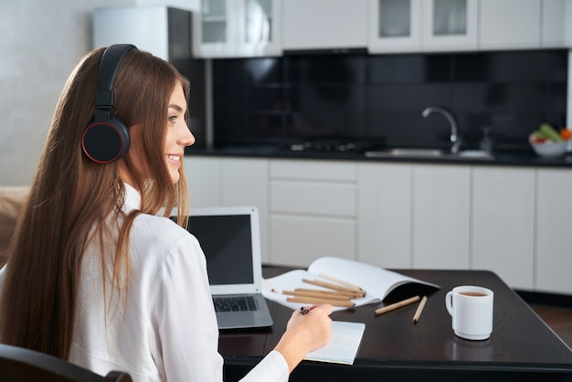 Side view of smiling young woman wearing modern headphones during online education on laptop