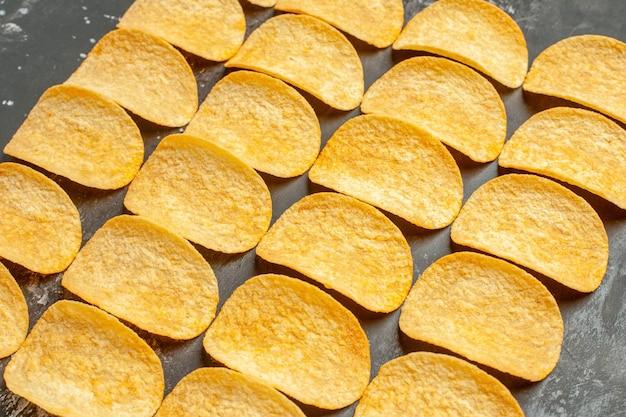 Vista laterale dello spuntino party per gli amici con deliziose patatine fritte sul tavolo grigio