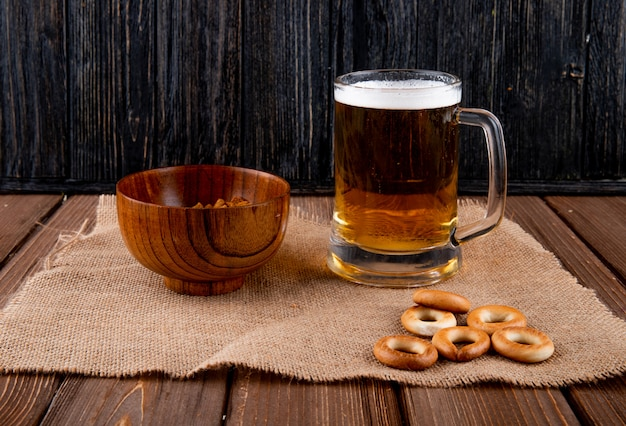 Side view snacks for beer hard chuck in bowl and crackers with mug of beer on wooden table