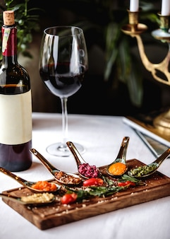 Side view snacks on a blackboard with a bottle and a glass of red wine
