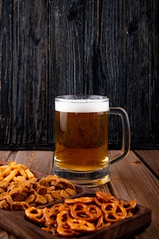 Вид сбоку закуски к пиву жареные чипсы и мини-брезель с кружкой пива на деревянном столе