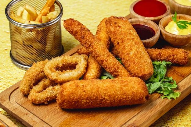 La vista laterale fa un spuntino gli anelli di cipolla che la mozzarella attacca le patate fritte e le salse su un bordo