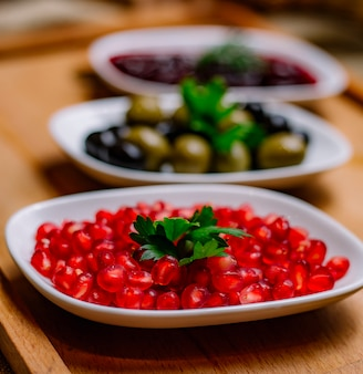Side view snacks pomegranate black and green olives and sauce on the table
