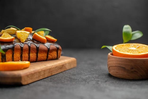 Vista laterale di torte morbide e arance tagliate con foglie sul tavolo scuro