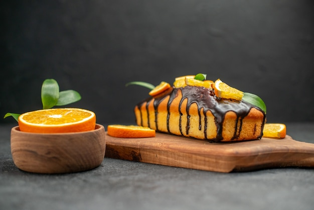 Side view of soft cakes on cutting board and cut orangeswith leaves on dark table