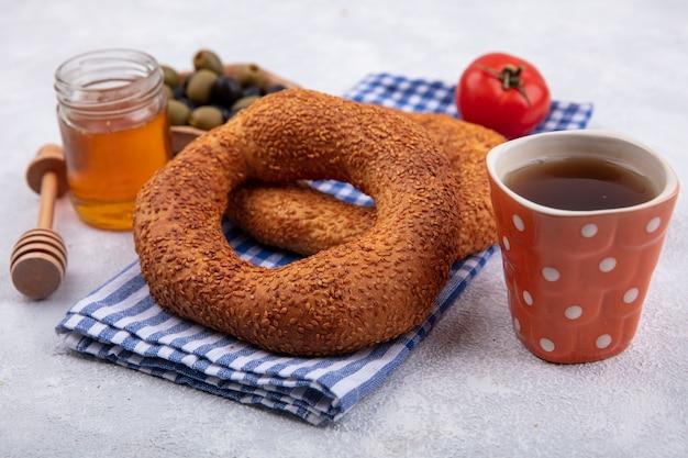 Vista laterale del morbido tradizionale bagel turco isolato su un panno controllato con un pomodoro e olive su una ciotola di legno con miele su un vasetto di vetro su sfondo bianco