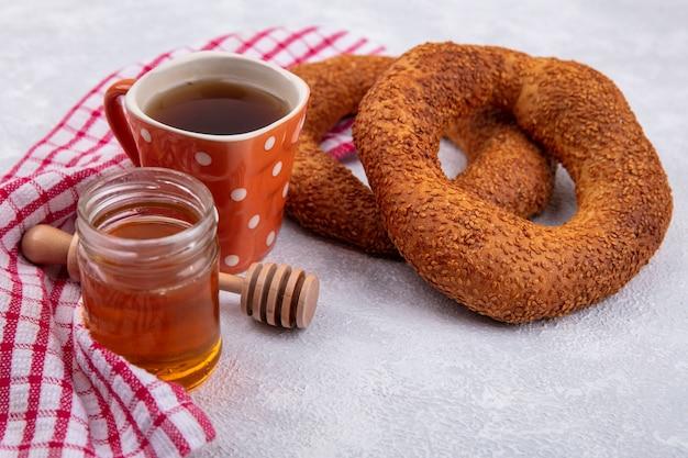 Vista laterale di morbidi bagel turchi con una tazza di tè e miele su un vasetto di vetro su un panno rosso controllato su sfondo bianco