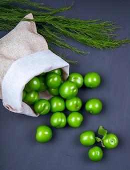 Vista laterale di prugne verdi acide sparse da un sacco con finocchio sul tavolo nero