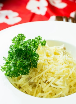 Side view of spaghetti bolognese with parmesan in white bowl on colorful