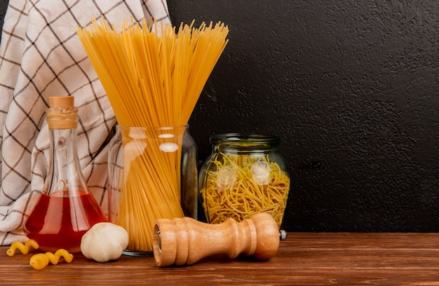 Side view of spaghetti pasta in jars with melted butter garlic salt and plaid cloth on wooden surface and black background with copy space