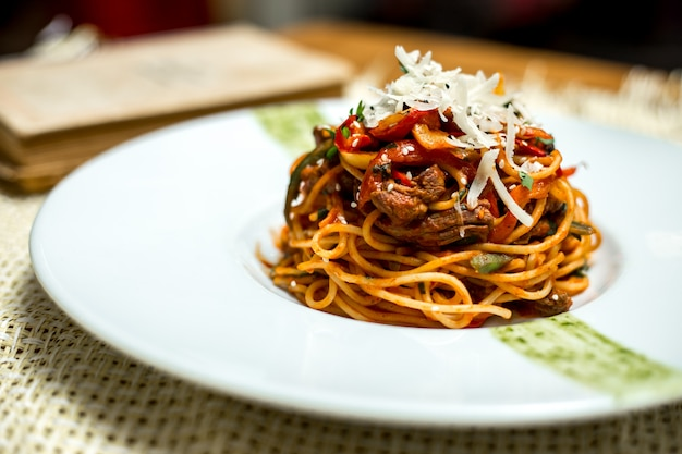 Side view spaghetti with meat and grated cheese