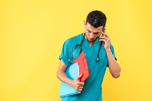 Специалист, вид сбоку, врач с документами разговаривает по телефону с пациентом