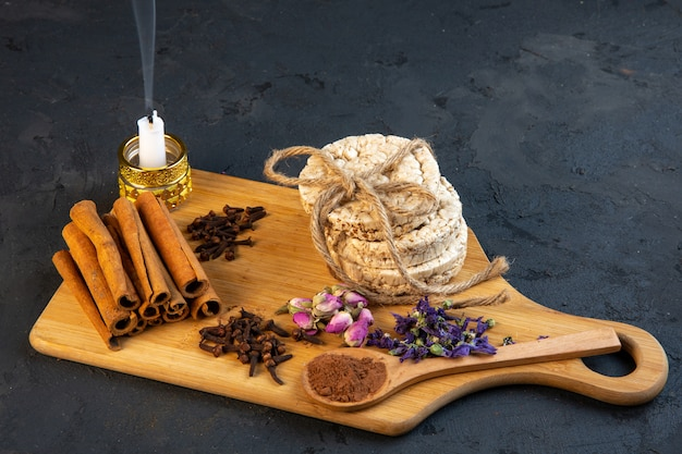 Side view of spice cloves with cinnamon sticks rice breads tied with a rope rose tea and candle on wooden board