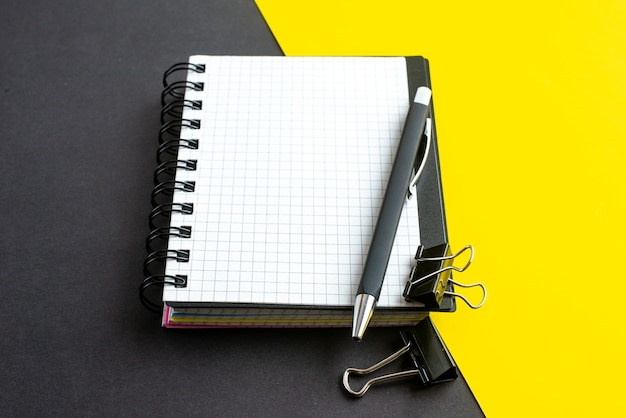 Side view of spiral notebook on book and pens on black yellow background with free space