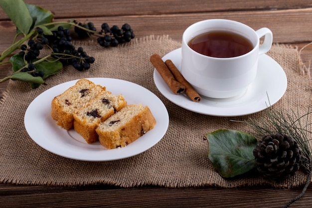 Side view of sponge cake slices on a plate with a cup of black tea on rustic