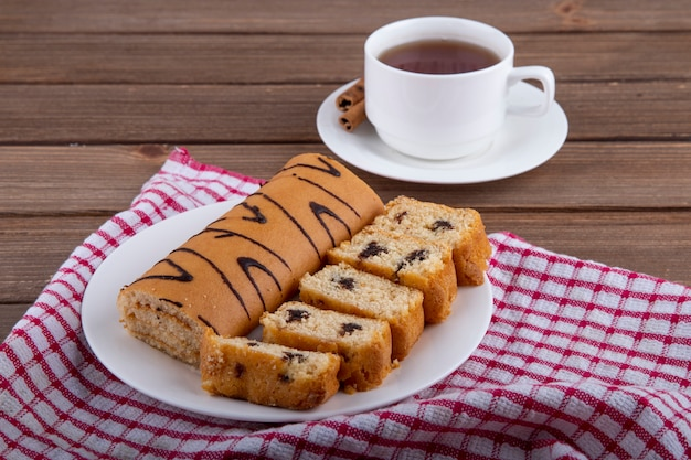 Side view of sponge cakes with chocolate on a white plate and a cup of tea on wooden