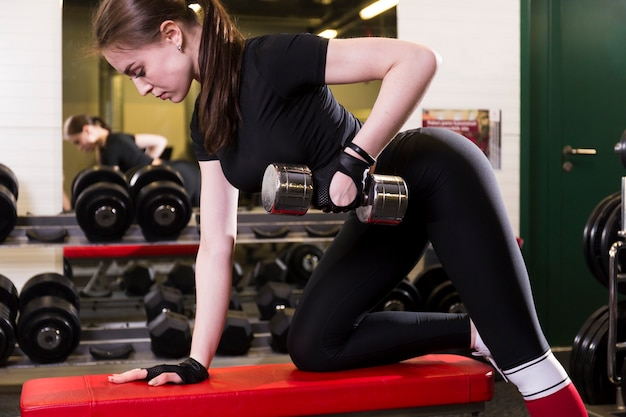 Side view of a sportive young woman doing exercise with dumbbell