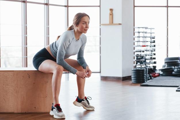 Вид сбоку. спортивная молодая женщина имеет фитнес-день в тренажерном зале в утреннее время