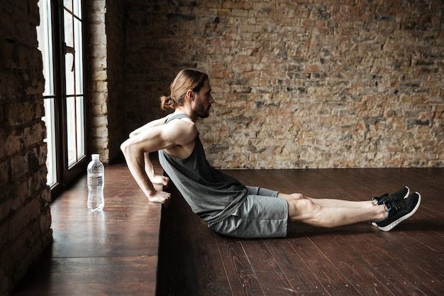 Side view of a sportsman doing exercises at the windowsill