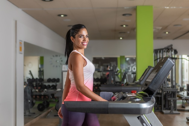 Side view of a sportswoman looking at camera walking on a treadmill at gym.