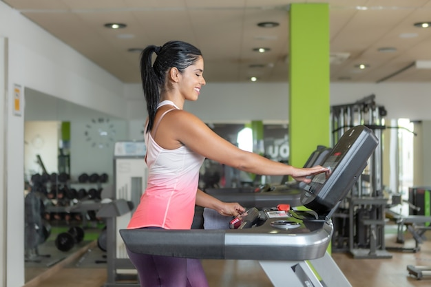 Side view of a sportswoman using a treadmill at gym touching the panel of machine.