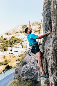 Side view of sporty man climbing on rock