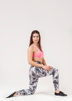 Side view of sporty woman posing in gym clothes
