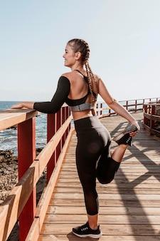 Vista laterale della donna sportiva che si estende sulla spiaggia