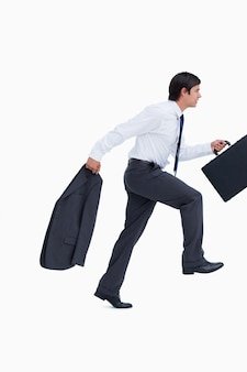 Side view of sprinting businessman with suitcase and jacket
