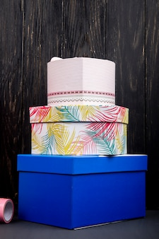 Side view of a stack of colorful present boxes at dark wooden table