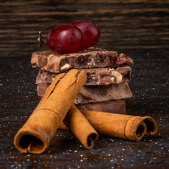 Side view of stack of milk and dark chocolate with nuts fruits and berries and cinnamon sticks on dark background