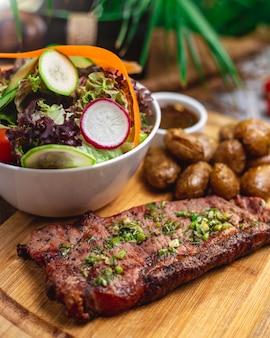 Вид сбоку кола с салатом на гриле из красного мяса с огурцом, редисом, помидорами, салатом, зеленью и жареным картофелем на столе