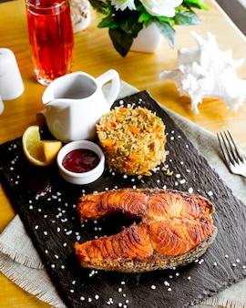 Вид сбоку стейк из жареной красной рыбы с рисом с овощами ломтиком лимона и гранатовым соусом на доске