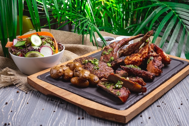 Стейк с жареными ребрышками, жареной курицей и картофелем на доске, с овощным салатом