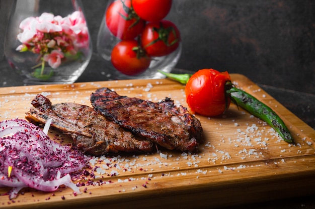 Side view steak with tomato and onion in steak board