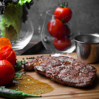 Side view steak with tomato and paper and spicy sauce in steak board